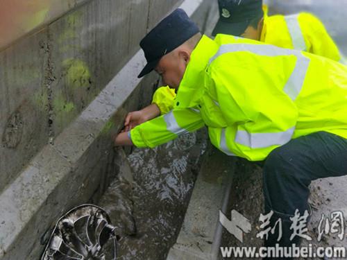 襄阳东津公安民警徒手疏通被堵泄水孔
