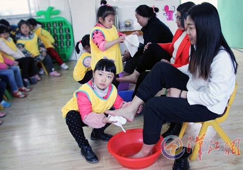 樊西教工幼儿园的小朋友在为妈妈洗脚.